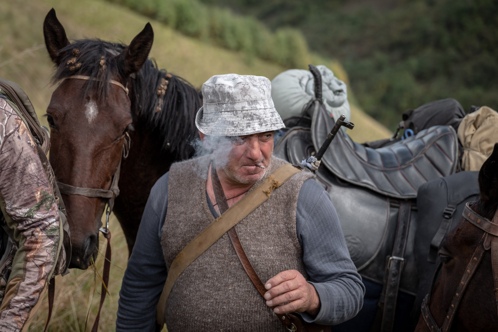 caccia al tur: la guida fuma una sigaretta, subito dietro i cavalli