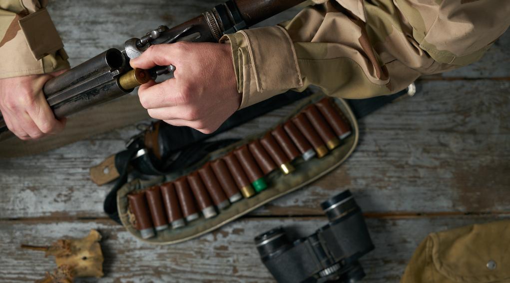 legge sulle armi: cacciatore prepara fucile e munizioni