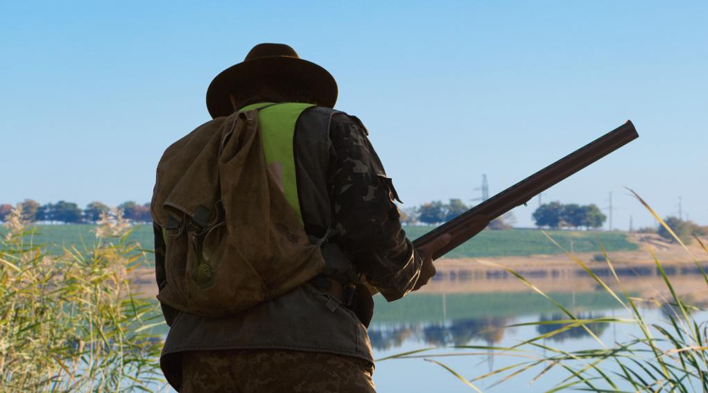 Caccia nelle aree Rete Natura 2000: cacciatore di spalle in zona umida