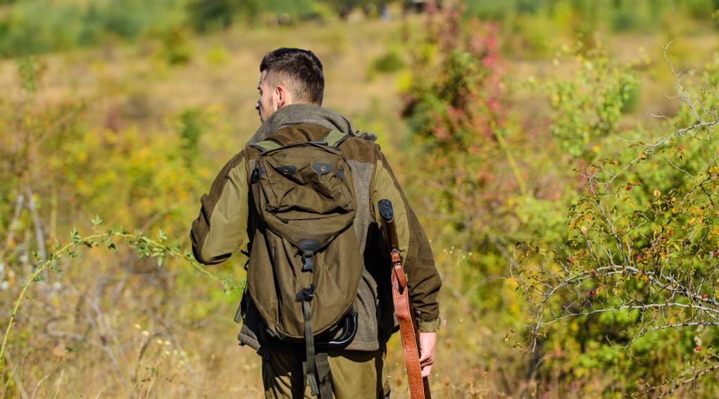 prossimi calendari venatori: cacciatore di spalle con fucile e zaino