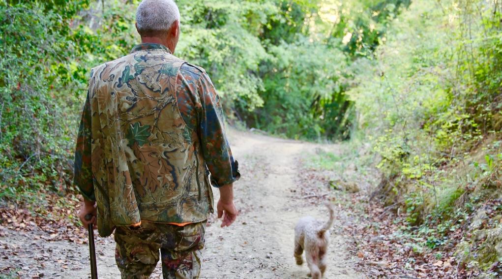 piano faunistico-venatorio delle Marche: cacciatore di spalle dietro a cane