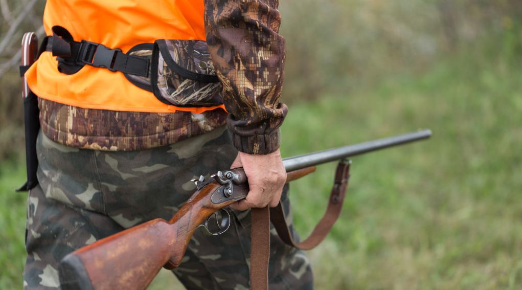 calendario venatorio della Liguria: cacciatore con gilet alta visibilità e fucile nella mano destra