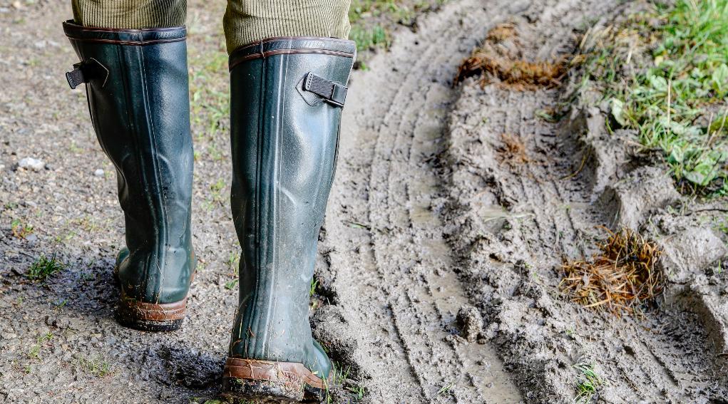 incidente di caccia: stivali di cacciatore che cammina su terreno fangoso