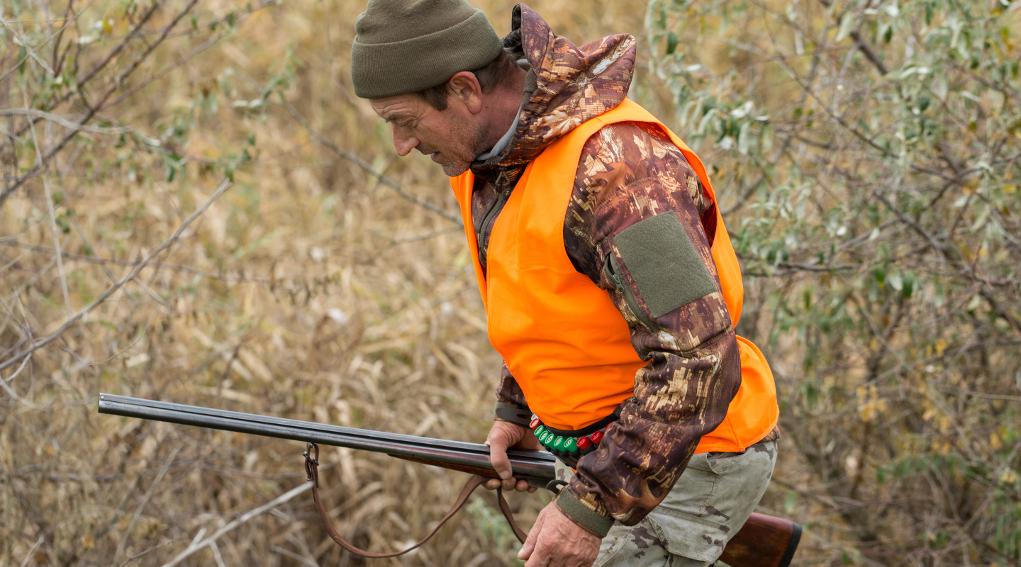Divieto di caccia in fondo privato: cacciatore in alta visibilità con fucile in mano