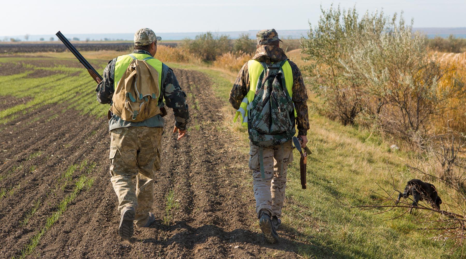 Le notizie di caccia della settimana: due cacciatori di spalle con cane da caccia