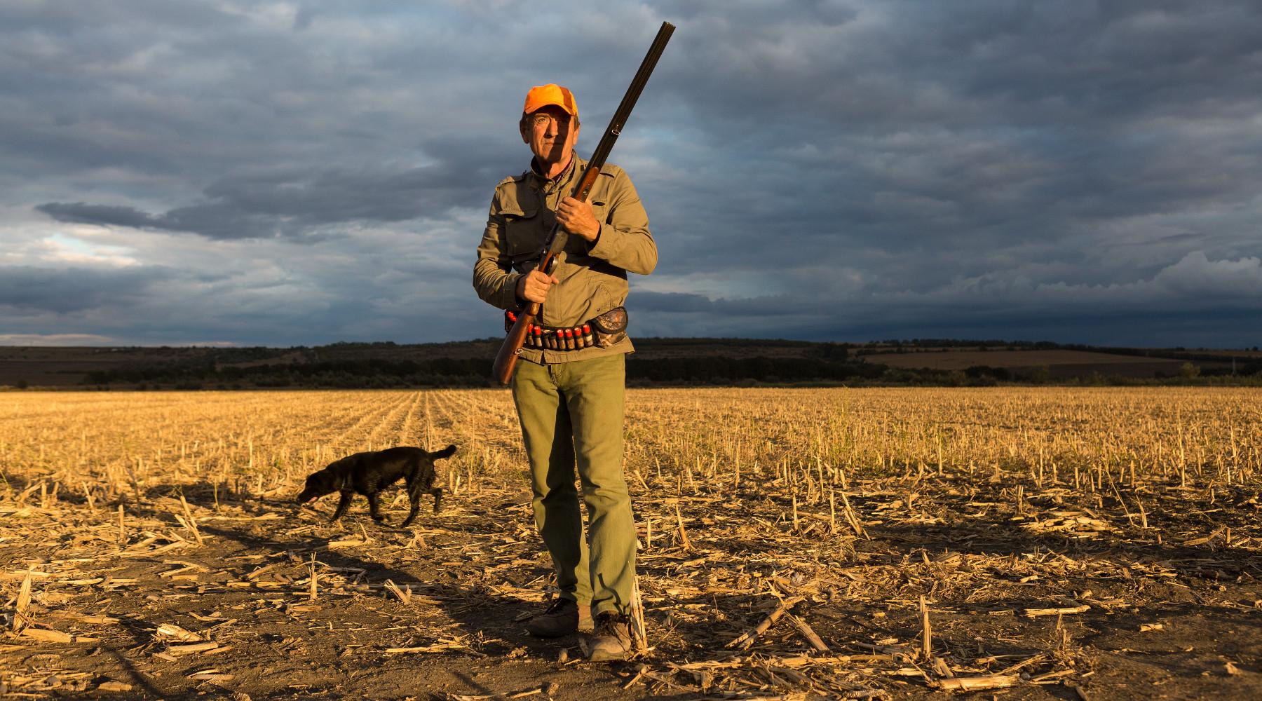 calendario venatorio della Toscana: cacciatore con fucile, cane alle sue spalle, al tramonto