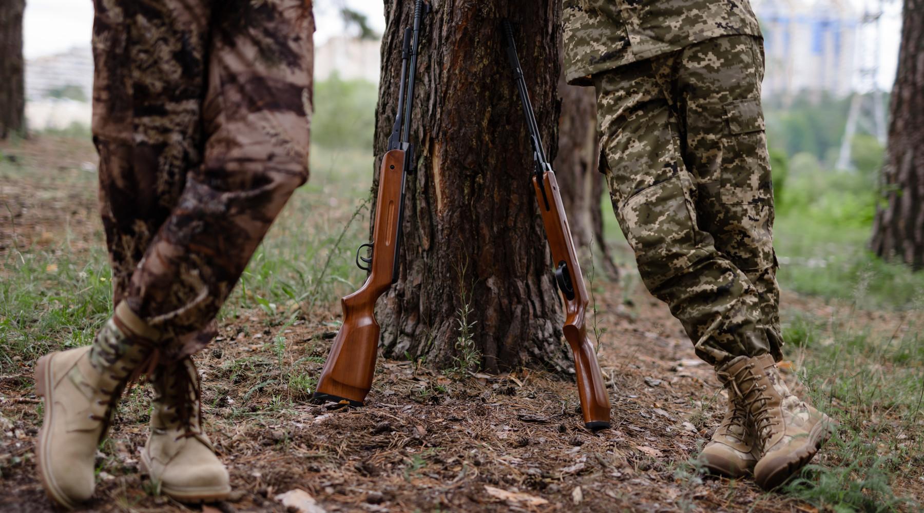 Misure anticontagio: due cacciatori appoggiati al tronco di un albero
